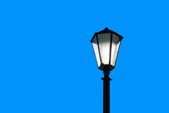 Sunlit street lamp  against blue background Royalty Free Stock Images