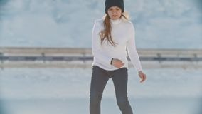 Sunlit teen girl skillfully skating on outdoor public ice rink. Youth pastime and rest stock footage