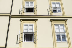 Sunlit wall of office building in the morning with open windows Royalty Free Stock Images