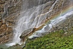 Sunlit waterfall in the Austrian Alps with rainbow long time exposure. Sunlit waterfall in the Austrian Alps with rainbow at the bottom long time exposure Royalty Free Stock Image