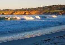 Sunlit Wellen und Klippen Stockfoto