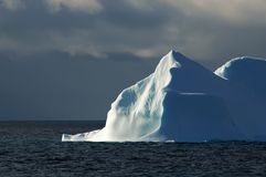 Sunlit white-blue iceberg with dark sky royalty free stock images