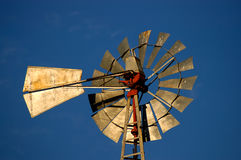 Sunlit windmill. Windmill blades illuminated by the sun against a blue sky stock image
