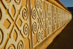 Sunlit yellow stone banister with white pattern Royalty Free Stock Photo