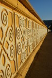 Sunlit yellow stone banister with white pattern Stock Images