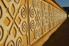 Sunlit yellow stone banister with white pattern Royalty Free Stock Photography
