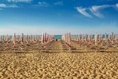 Sunlongers on the sandy beach. Withdrawn yellow umbrellas and sunlongers on the sandy beach in Italy Stock Photo