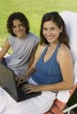 照顾坐sunlounger使用膝上型计算机户外与儿子(13-15)画象。 免版税库存照片