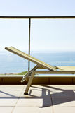 Sunlounger in a balcony. Closeup of a sunlounger in a balcony, with the ocean in the background Royalty Free Stock Photo