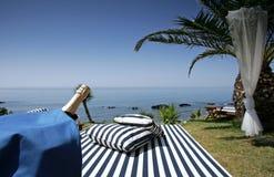 Sunlounger de Champagne et vues ensoleillées de mer Image stock