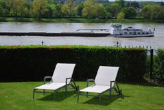 Sunlounger in a garden direct at the river. With a cargo ship on the river Stock Photography