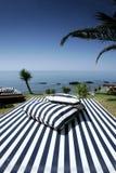 Sunlounger a strisce e viste piene di sole del mare Immagini Stock Libere da Diritti