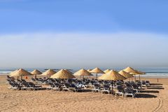 Sunlounger and sunshades in a row on the beach Royalty Free Stock Photos