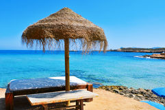 Sunlounger and umbrella in Ibiza Island, Spain. Detail of a relaxing area in a Cala Conta beach in Ibiza Island, Spain, with a comfortable sunlounger and a Royalty Free Stock Photos