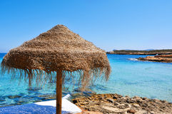 Sunlounger and umbrella in Ibiza, Spain. Detail of a relaxing area in a beach in Ibiza, Spain, with a comfortable sunlounger and a rustic umbrella made of Royalty Free Stock Photo