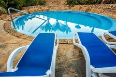 Sunloungers и бассейн с отраженными ладонями в воде Стоковое Фото