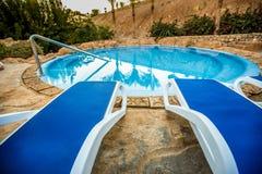Sunloungers и бассейн с отраженными ладонями в воде Стоковая Фотография