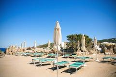 Sunloungers и зонтики в Baja Сардинии, Италии Стоковые Изображения RF
