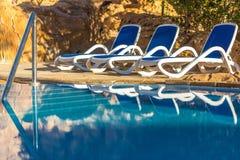 Sunloungers около бассейна и отраженное их внутри открытому морю Стоковое Изображение RF