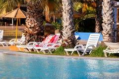 Sunloungers en piscina Foto de archivo libre de regalías