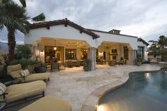 Sunloungers na piscina da casa moderna foto de stock