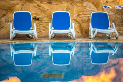 Sunloungers near swimming pool and reflected their in blue water Royalty Free Stock Photo