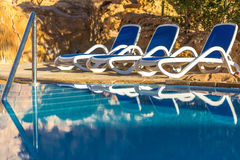 Sunloungers near swimming pool and reflected their in blue water Royalty Free Stock Image