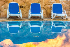 Sunloungers near swimming pool and reflected their in blue water Royalty Free Stock Photography
