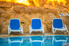 Sunloungers near swimming pool and reflected their in blue water Stock Photo