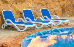 Sunloungers near swimming pool and reflected their in blue water Stock Image