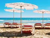 Sunloungers och paraplyer i en tyst strand Arkivfoton