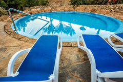 Sunloungers and swimming pool with reflected palms in water Stock Photo
