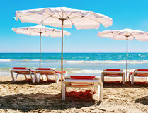 Sunloungers and umbrellas in a quiet beach Stock Photos