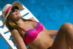 Sunning at poolside. Pretty smiling woman with hat and sunglasses is sunning at the poolside stock image