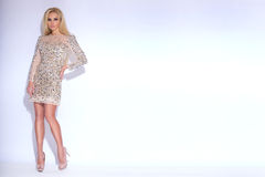 Sunning beautiful young woman blond long hair and of short elegant dress with glowing crystals. And iridescent sequins on a white background stock photos