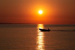 Sunnrise with fishermans boat in sunlight way on sea surface. stock images