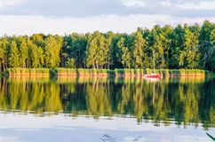 A sunny afternoon by the lake. Summer landscape with boat on the water royalty free stock photography