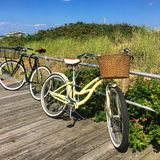 On a sunny afternoon. Two bikes rest against a rail on a boardwalk along the Jersey Shore Stock Photos