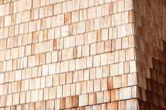 Sunny alpine wooden clapboard wall. Traditional alpine wooden shingle wall in the sun stock photos
