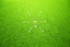 Sunny artificial green grass with light bulb arrows Royalty Free Stock Photo