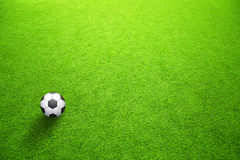 Sunny artificial green grass with soccer ball Royalty Free Stock Photography