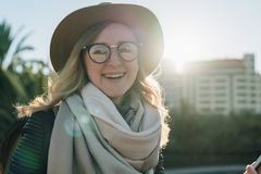 Sunny autumn day, backlight. Young attractive woman tourist in hat, eyeglasses and with backpack stands on city street. royalty free stock photo