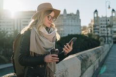 Sunny autumn day, backlight. Young attractive woman tourist in hat, eyeglasses and with backpack stands on city street stock photos