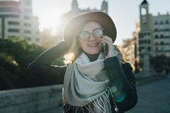 Sunny autumn day, backlight. Young attractive woman tourist in hat and eyeglasses stands on city street royalty free stock photo