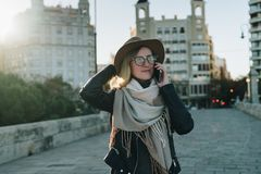 Sunny autumn day, backlight. Young attractive woman travels in hat and eyeglasses stands on city street royalty free stock images