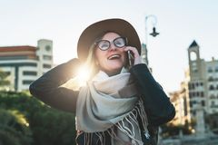 Sunny autumn day, backlight. Young woman travels in hat and eyeglasses stands on city street, talking on cell phone. Sunny autumn day, backlight. Young Stock Photography