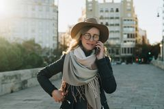 Sunny autumn day, backlight. Young attractive woman travels in hat and eyeglasses stands on city street royalty free stock photography