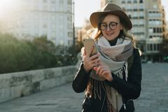 Sunny autumn day, backlight. Young attractive woman travels in hat and eyeglasses stands on city street, uses smartphone. Hipster girl is looking for road Royalty Free Stock Photos