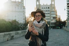 Sunny autumn day, backlight. Young attractive woman travels in hat and eyeglasses stands on city street, uses smartphone. Hipster girl is looking for road Stock Photography