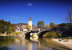 Sunny autumn day on Lake Bohinj, Slovenia. Sunny autumn day on Lake Bohinj in Sloveniaa, with golden and orange trees, blue sky and water Royalty Free Stock Images